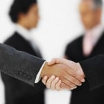 Close-up of the hands of two businesswomen shaking hands with two businessmen in background